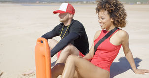 Smiling lifeguards sitting on beach Royalty Free Stock Image