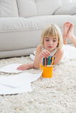 Smiling litlle girl drawing lying on the floor Royalty Free Stock Images