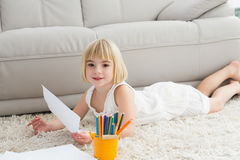 Smiling litlle girl drawing lying on the floor Stock Photos