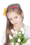Smiling litlle girl with spring flowers. Picture of smiling litlle girl with white tulips in hands over white Royalty Free Stock Image
