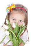 Smiling litlle girl with spring flowers. Picture of smiling litlle girl with white tulips in hands over white Royalty Free Stock Photo