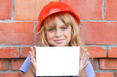 Smiling littl girl with helmet and white card Stock Image