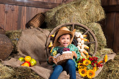 Smiling little african girl in cowboy hat sitting in the hay Royalty Free Stock Images