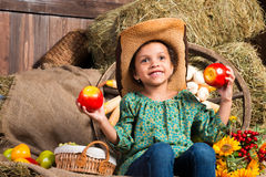 Smiling little african girl in cowboy hat sitting in the hay with apples Stock Photo