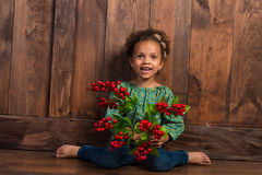 Smiling little african  girl in rural shirt with bunch of berries on  background of brown wooden wall Stock Photo