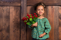 Smiling little african  girl in rural shirt with bunch of berries on  background of brown wooden wall Royalty Free Stock Photos