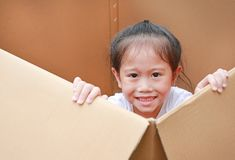 Smiling little Asian child girl lie in big cardboard box.  stock photo