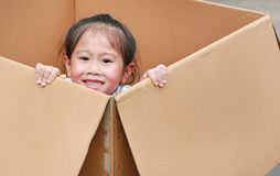 Smiling little Asian child girl lie in big cardboard box.  royalty free stock image