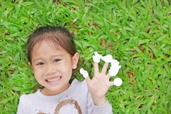 Smiling little Asian child girl lying on green grass lawn with showing empty white stickers on her fingers stock image