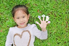 Smiling little Asian child girl lying on green grass lawn with showing white stickers with number one to five on her fingers royalty free stock photo