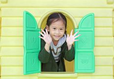 Smiling little Asian child girl playing with window toy playhouse in playground.  royalty free stock photography
