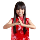 Smiling little asian girl with cheongsam respecting on chinese n Royalty Free Stock Photo