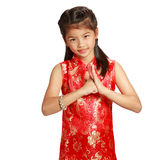 Smiling little asian girl with cheongsam respecting on chinese n Royalty Free Stock Images