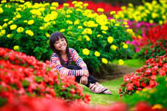 Smiling little asian girl sitting on flower field Stock Photos