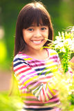 Smiling little asian girl standing on flower field Royalty Free Stock Image