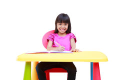 Smiling little asian girl writing on the desk Royalty Free Stock Photos