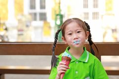 Smiling little Asian kid girl enjoy eating ice cream cone with stains around her mouth.  stock image