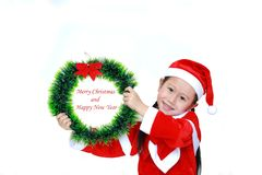 Smiling little Asian kid girl in Santa costume dress with holding Christmas round wreath on white background. Merry Christmas and. Happy New Year Concept stock photography