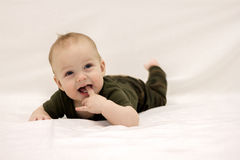 Smiling little baby boy on the bed royalty free stock photo
