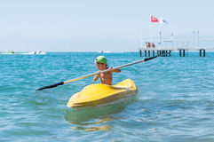 Smiling little baby boy in green baseball cap kayaking at tropical ocean sea in the day time. Royalty Free Stock Photography