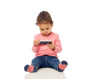 Smiling little baby girl playing with smartphone Royalty Free Stock Photos