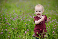 Smiling little baby in a meadow. Happy little baby girl in a meadow eating cookie Royalty Free Stock Photos