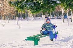 Little baby with a shovel walking alone in the park. Winter season. royalty free stock photo