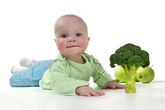 Smiling little baby on white table with broccoli. Nutrition of newborns stock photos