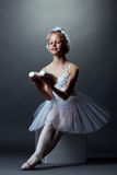 Smiling little ballerina posing sitting on cube Stock Images