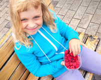 Smiling little blond girl with raspberries Stock Photos