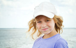 Smiling little blond girl on the sea coast Stock Photography