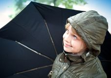 Smiling little blond girl with umbrella. Portrait of a smiling little blond girl with umbrella in a casual jacket with the hood Stock Photo