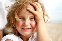 Smiling little blonde girl. Girl with blue eyes smiling and looking straight to the camera royalty free stock photography