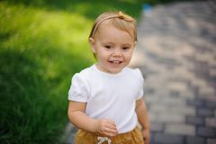 Smiling little blonde girl with cute headband. Walking outdoors near the fresh green grass lawn Royalty Free Stock Image