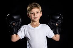 Smiling little boxer fighter portrait in black boxing gloves with hands up. The little winner.  Stock Photography