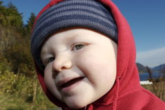 Smiling little boy. A young boy smiling and wearing a hat royalty free stock image