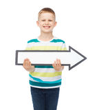 Smiling little boy with blank arrow pointing right Royalty Free Stock Image