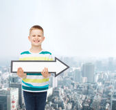 Smiling little boy with blank arrow pointing right Stock Image