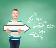 Smiling little boy with blank arrow pointing right Royalty Free Stock Photo