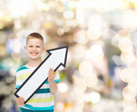 Smiling little boy with blank arrow pointing right Stock Photo