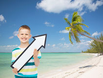 Smiling little boy with blank arrow pointing right Royalty Free Stock Images