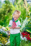 Smiling little boy with blond hair holding american flag. And looking at it in sunny park or garden on summer day. Portrait of child on blurred background stock photos