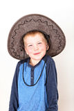 Smiling little boy with blue shirt and large brown hat Royalty Free Stock Images