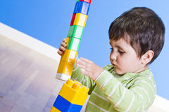 A smiling little boy is building a toy block Stock Image