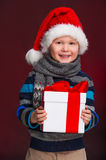 Smiling little boy with Christmas gift in his hand. Royalty Free Stock Image