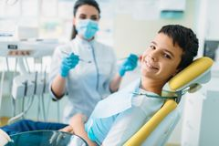 Smiling little boy in a dental chair. Professional pediatric dentistry, children stomatology, female dentist on background stock images