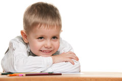 Smiling little boy at the desk Royalty Free Stock Images