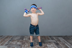 Smiling little boy doing exercises with dumbbells Stock Images