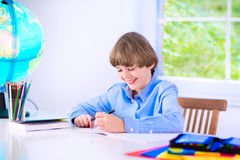 Smiling little boy doing homework Royalty Free Stock Photos