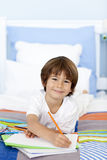 Smiling little boy drawing in bed Royalty Free Stock Photography